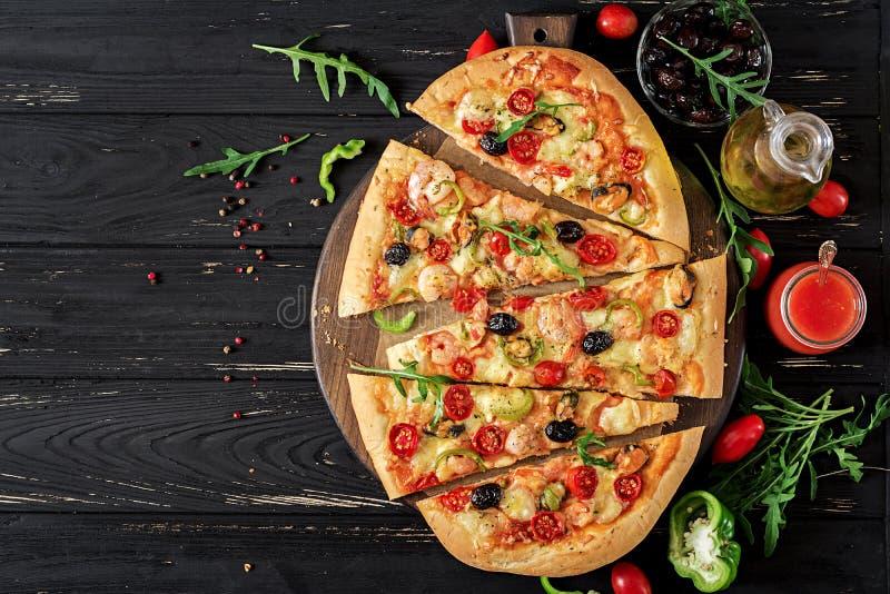 Очень вкусная пицца креветок и мидий морепродуктов на черном деревянном столе варящ ингридиенты еды итальянские стоковые изображения