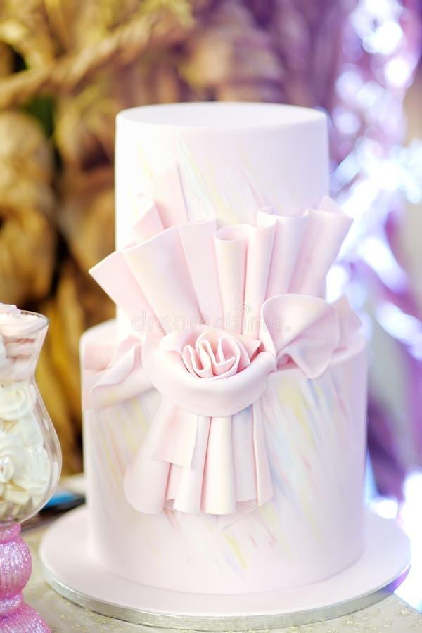 Очень вкусная розовая свадьба или именниный пирог украшенный со смычком стоковые фото