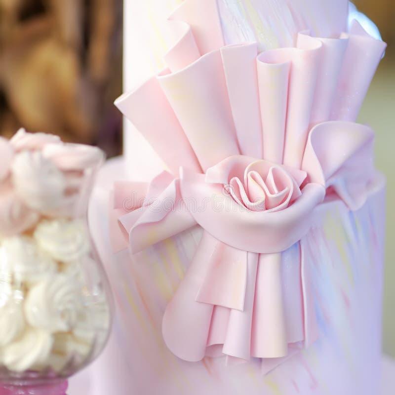 Очень вкусная розовая свадьба или именниный пирог украшенный со смычком стоковая фотография