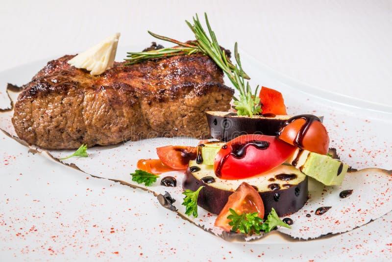Очень вкусное барбекю Аппетитная большая часть зажаренных в духовке мяса, овощей, соуса и трав, на белой плите Горизонтальная рам стоковое фото rf