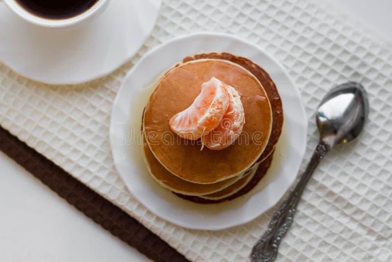 Очень вкусные блинчики с медом и чашкой кофе на белой плате стоковое фото