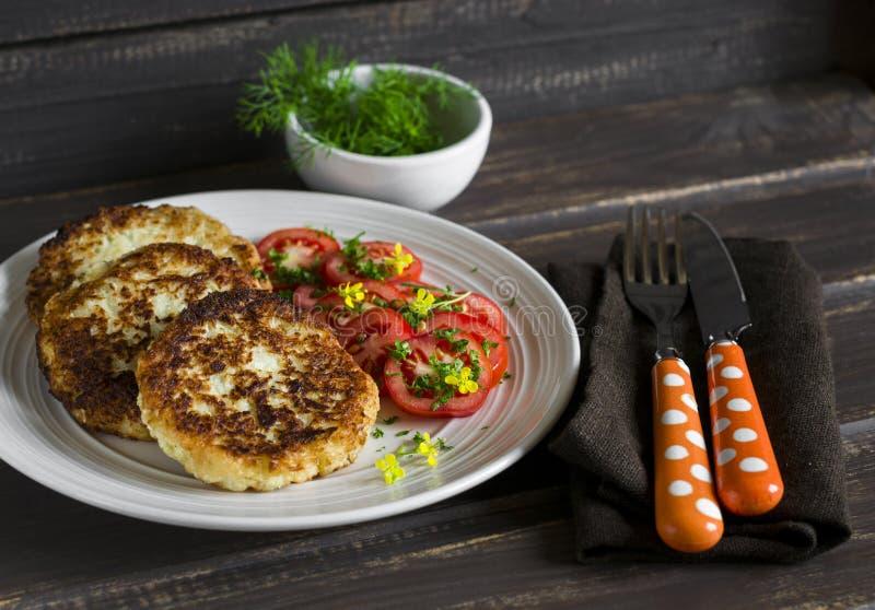 Очень вкусные вегетарианские котлеты капусты и свежие томаты на тонкой жести стоковая фотография