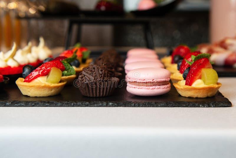 Очень вкусные десерты на черном подносе Ресторанное обслуживание стоковая фотография rf
