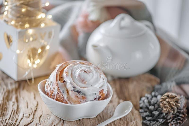 Очень вкусные домодельные сладкие плюшки с рождеством сахара циннамона и замороженности на старом деревянном столе Традиционные ш стоковая фотография