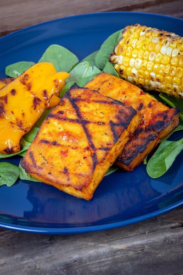 Очень вкусные зажаренные куски тофу с мозолью и желтым болгарским перцем стоковые изображения