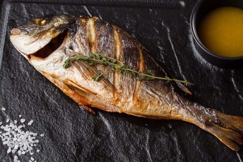 Очень вкусные зажаренные рыбы леща dorado или моря с кусками лимона, специями, розмариновым маслом на темном камне Зажаренные рыб стоковые изображения rf