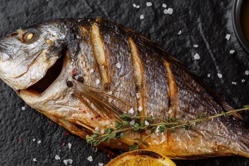 Очень вкусные зажаренные рыбы леща dorado или моря с кусками лимона, специями, розмариновым маслом на темном камне Зажаренные рыб стоковые изображения
