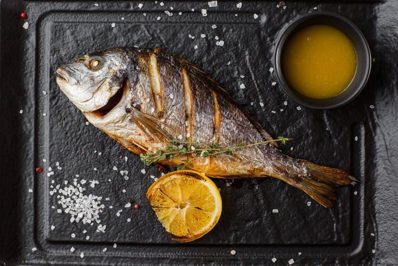 Очень вкусные зажаренные рыбы леща dorado или моря с кусками лимона, специями, розмариновым маслом на темном камне Зажаренные рыб стоковое изображение