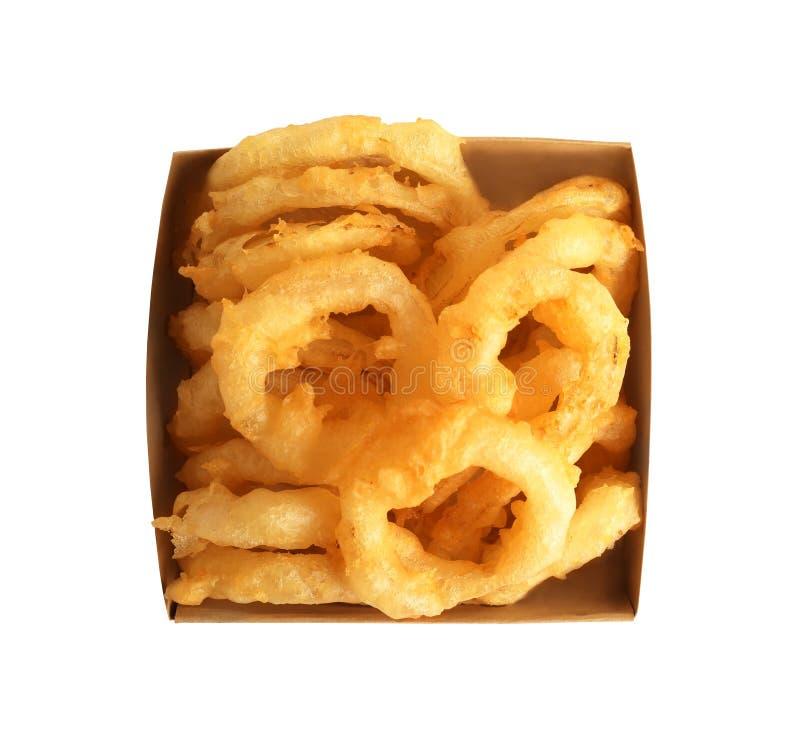 Очень вкусные золотые обвалянные в сухарях и глубоко зажаренные кудрявые кольца лука в картонной коробке на белой предпосылке стоковое изображение rf