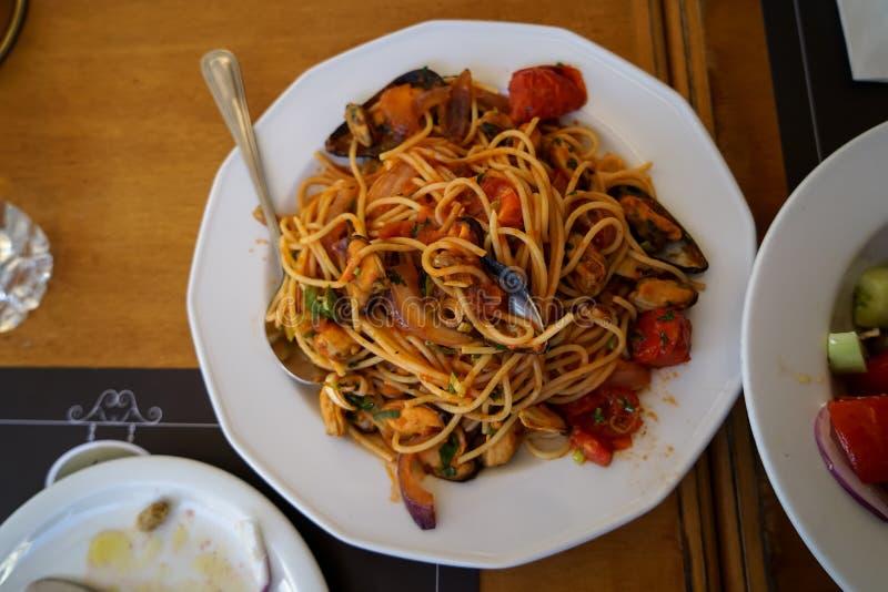 Очень вкусные макаронные изделия спагетти морепродуктов с мидией, кальмаром, креветкой, томатным соусом, etc Подача на белое блюд стоковое фото rf