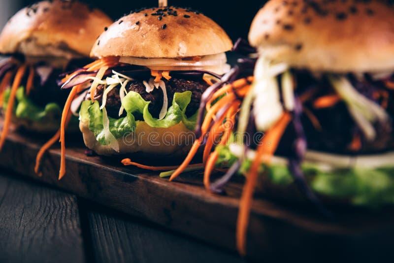 Очень вкусные домодельные гамбургеры с свежими овощами Тонизированное год сбора винограда стоковая фотография rf