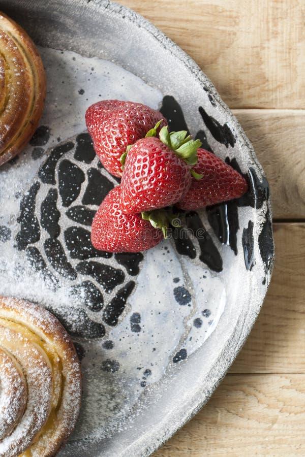 Очень вкусные плюшки взбрызнуты с порошком сахара и красным сочным str стоковые фотографии rf