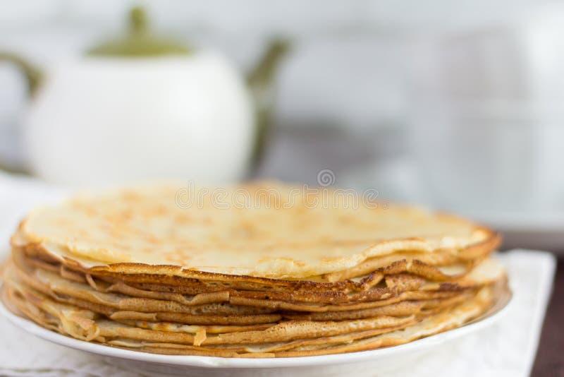 Очень вкусные свежие домодельные блинчики и утвари для чая на таблице стоковые фотографии rf