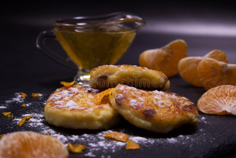 Очень вкусные чизкейки с изюминками от домодельного творога Украшенный с напудренным сахаром и пылом мандарина стоковая фотография