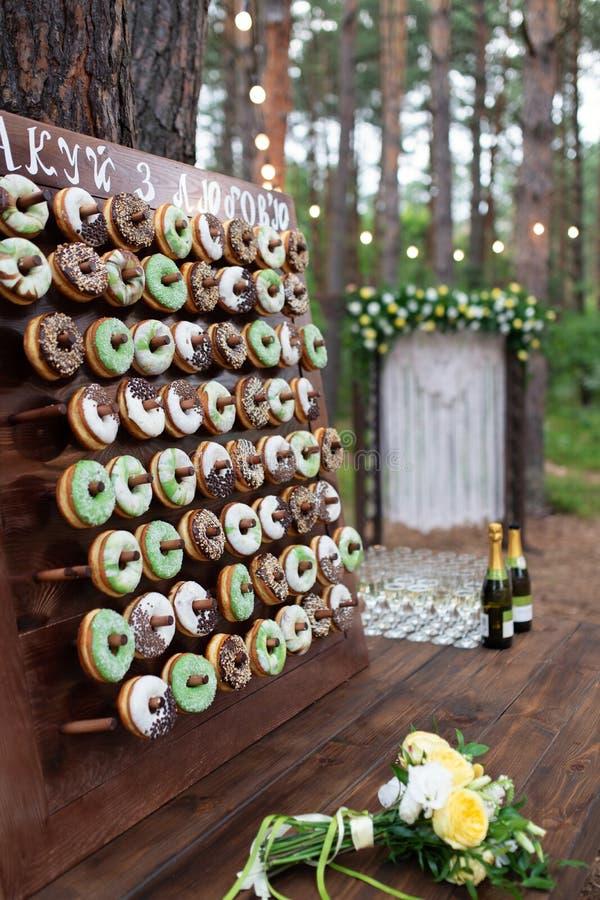 Очень вкусные donuts на деревянном stander Свадьба в оформлении свадьбы леса стоковые фотографии rf