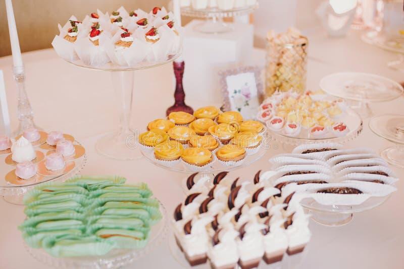 Очень вкусные eclairs, macaroons, пирожные, десерты и помадки на партии таблицы на приеме по случаю бракосочетания Белый и розовы стоковые фото