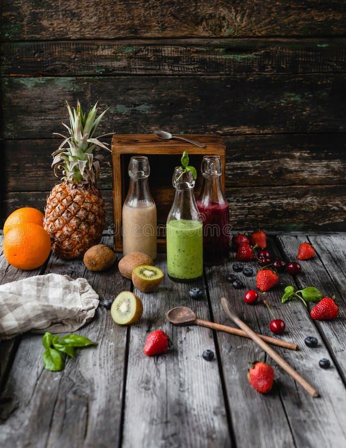 Очень вкусные smoothies вытрезвителя в стеклянных бутылках на деревенской деревянной доске стоковая фотография rf