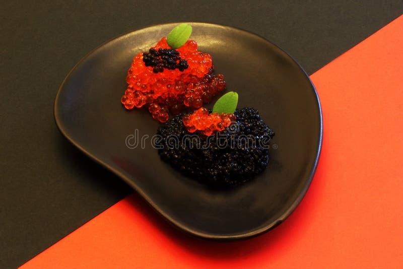 Очень вкусный аппетитный соленый красный цвет и черная икра с листьями мяты на черной керамической плите первоначальной формы на  стоковые изображения rf