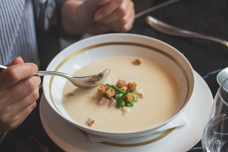 Очень вкусный белый луковый суп, человек готовый для того чтобы пробовать стоковая фотография