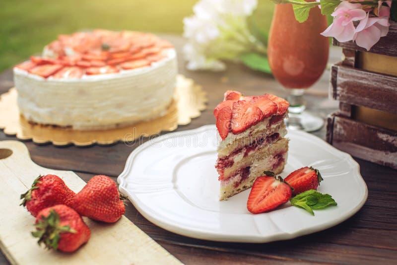 Очень вкусный домодельный торт лета с клубниками и сливк масла на деревянном крылечке и части на плите стоковое изображение