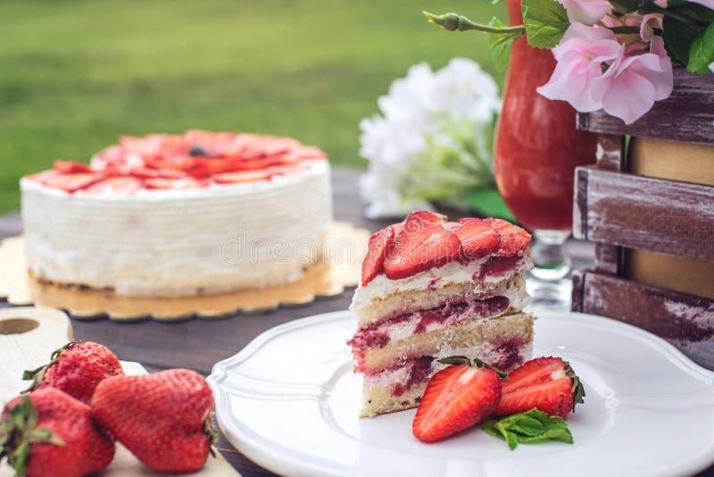 Очень вкусный домодельный торт лета с клубниками и сливк масла на деревянном крылечке и части на плите стоковые фото