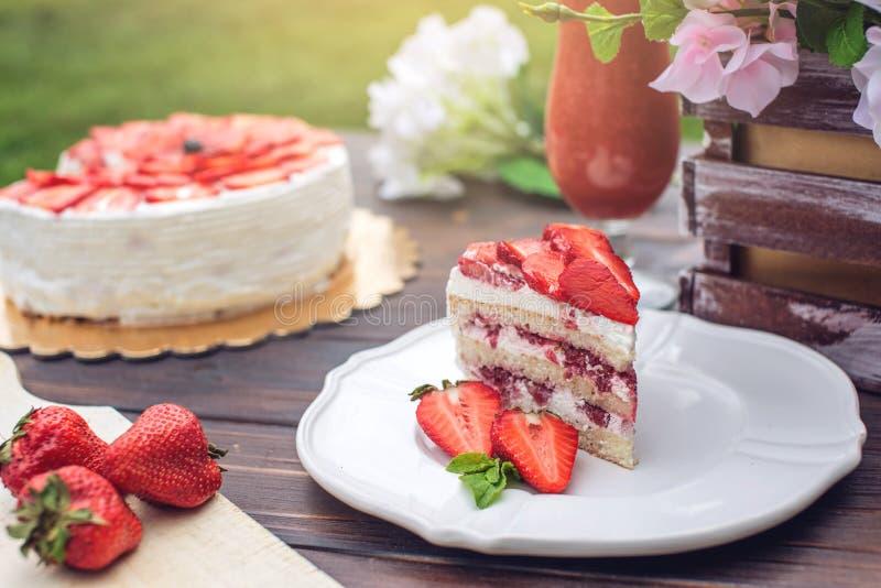 Очень вкусный домодельный торт лета с клубниками и сливк масла на деревянном крылечке и части на плите стоковая фотография rf