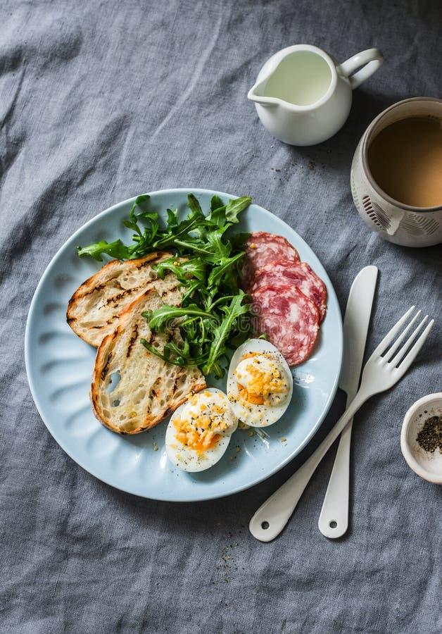 Очень вкусный завтрак или закуска - сосиска салями, вареное яйцо, arugula, зажаренный хлеб и кофе на серой предпосылке стоковая фотография