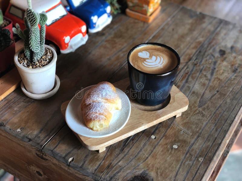 Очень вкусный завтрак; Кофе искусства Latte любов сердца в черных чашке и круассане покрыл с сахаром замороженности стоковые фото