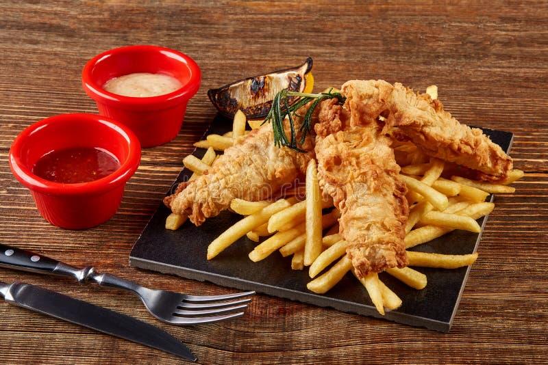 Очень вкусный золотой бэттер глубоко зажарил филе рыб и фраи француза, который служат на черной доске на деревянном worktop, взгл стоковое фото