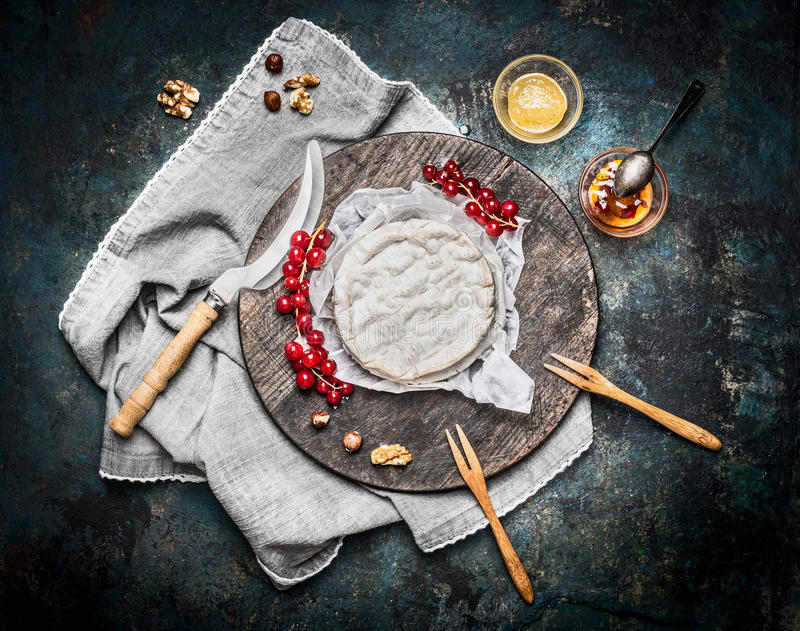 Очень вкусный зрелый сыр камамбера на деревянной разделочной доске с ягодами и соусом на деревенской предпосылке, взгляд сверху стоковое изображение