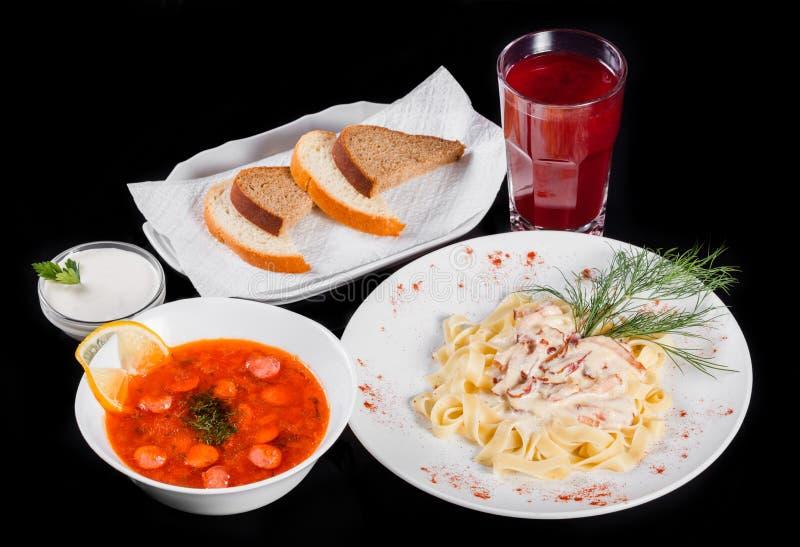 Очень вкусный обеденный стол с макаронными изделиями Fettuccine с мясом, горячим супом с сосисками, хлебом и компотом на черноте стоковое фото