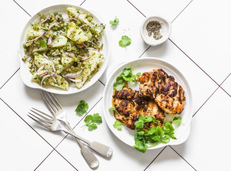 Очень вкусный обед - новые картошки, корнишоны, салат укропа и филе цыпленка барбекю на светлой предпосылке, взгляде сверху стоковая фотография