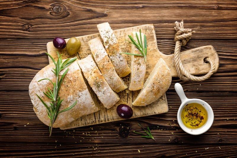 Очень вкусный домодельный итальянский хлеб ciabatta с оливковым маслом и оливками на деревянной деревенской предпосылке, над взгл стоковые изображения rf
