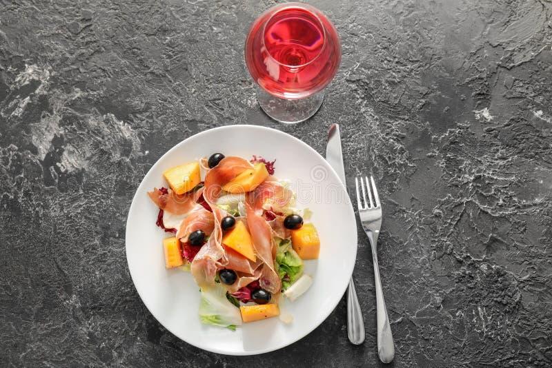 Очень вкусный салат дыни с ветчиной и бокал вина на серой таблице стоковые фото