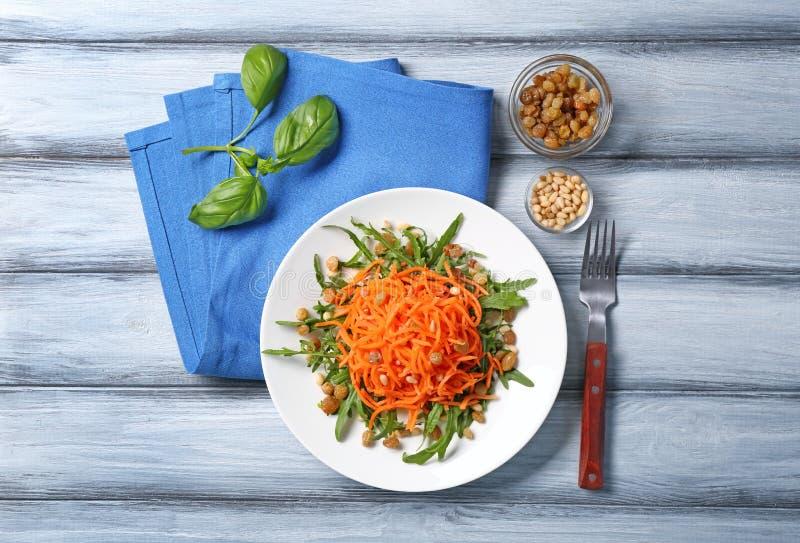 Очень вкусный салат изюминки моркови с зелеными цветами на деревянном столе стоковое фото