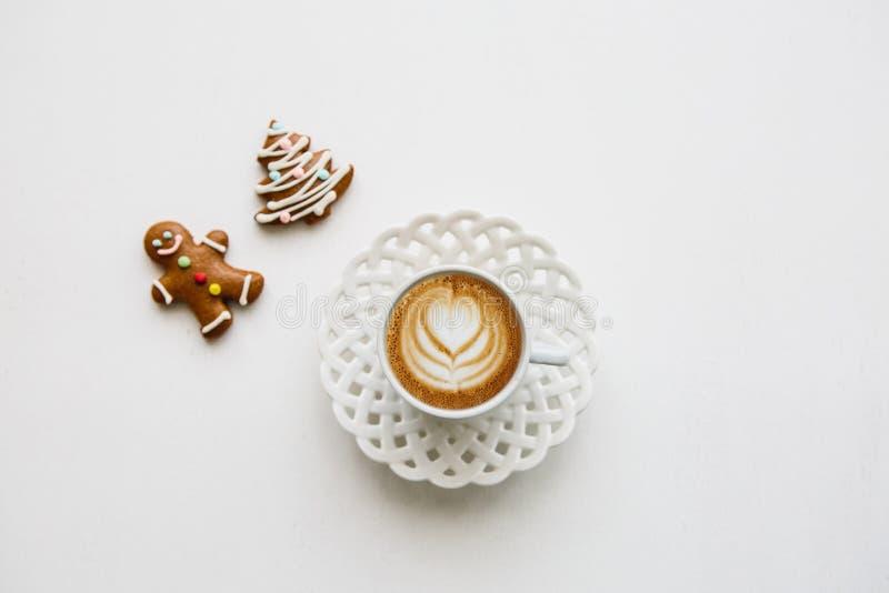 Очень вкусный свежий кофе капучино в кружке с картиной цветка Близрасположенные печенья пряника лож стоковое фото rf