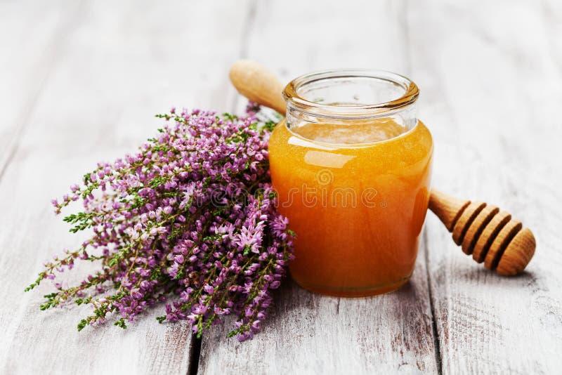 Очень вкусный свежий мед в баке или опарнике и вереске цветков на деревянной винтажной предпосылке стоковое изображение rf