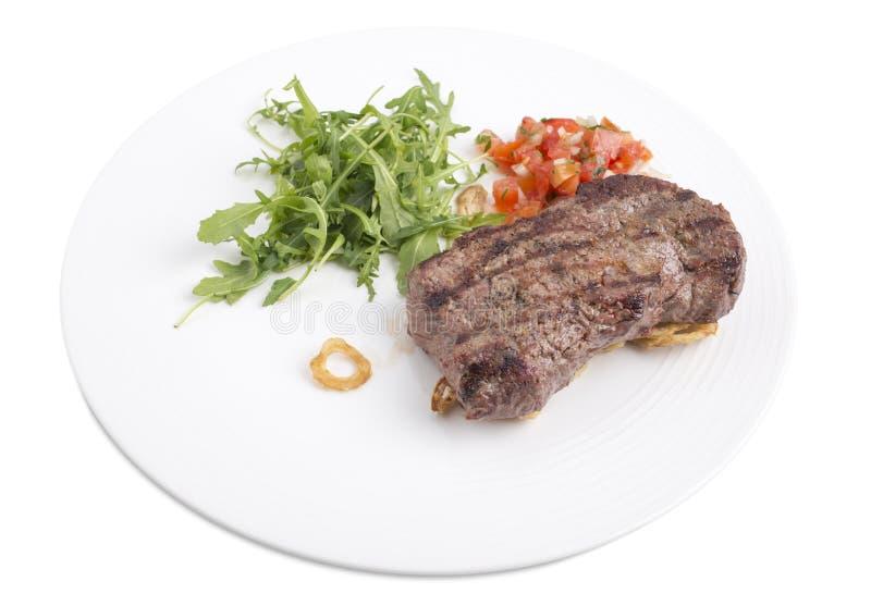 Очень вкусный стейк говядины с arugula в белой плите стоковое изображение rf