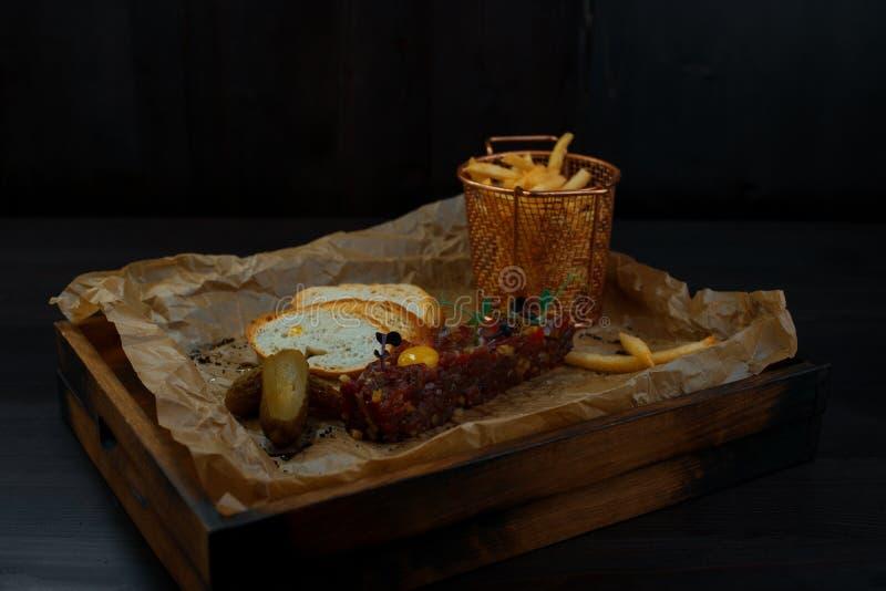 Очень вкусный тартар говядины с белыми кусками багета и французским картофелем фри с замаринованным огурцом на деревянной доске с стоковые изображения rf