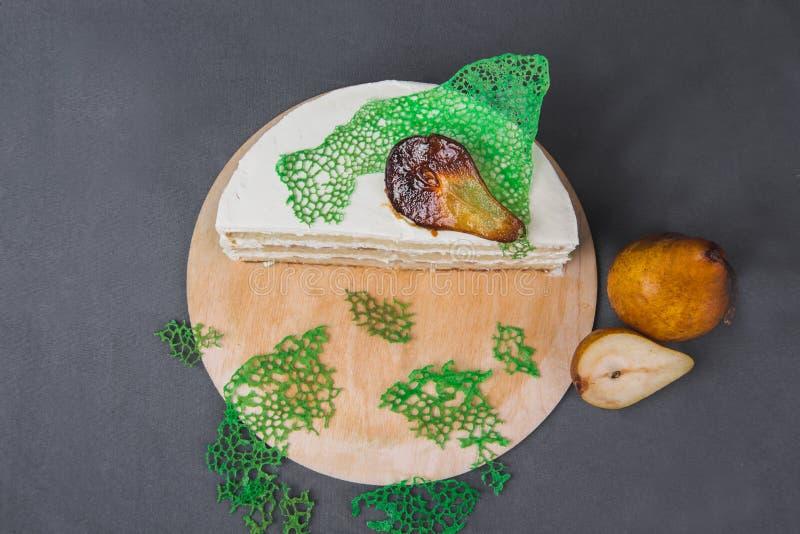 Очень вкусный торт украшенный с caramelized грушами на серой предпосылке стоковая фотография