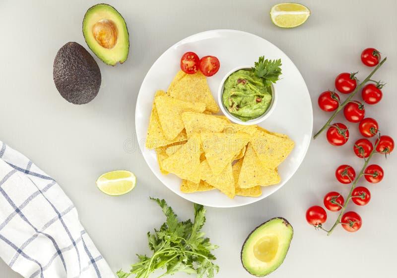 Очень вкусный шар гуакамоле рядом со свежими ингредиентами на таблице с обломоками tortilla Традиционный латино-американский мекс стоковое фото rf