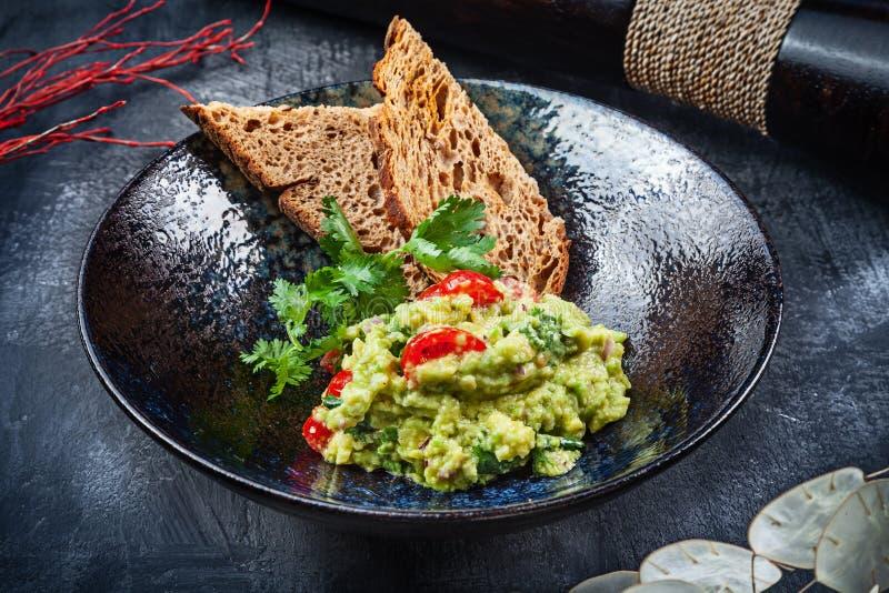 Очень вкусный шар гуакамоле с концом хлеба вверх на темной таблице с космосом экземпляра зеленый, естественно сделанный традицион стоковые изображения