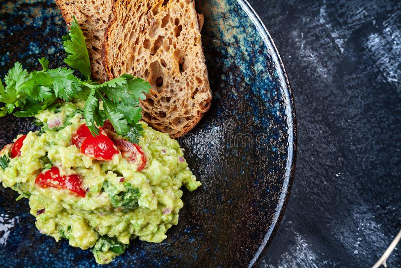 Очень вкусный шар гуакамоле с концом хлеба вверх на темной таблице с космосом экземпляра зеленый, естественно сделанный традицион стоковые фото