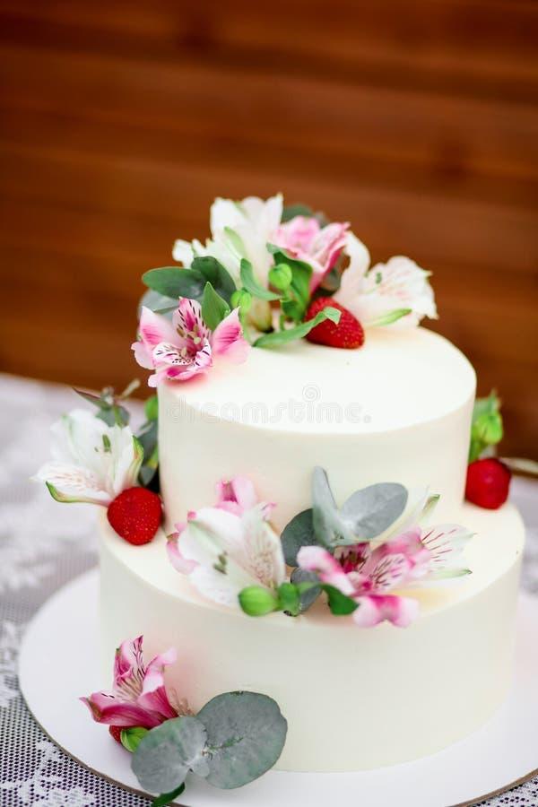 Очень вкусным замороженность украшенная свадебным пирогом белая с экзотическими цветками стоковое фото rf