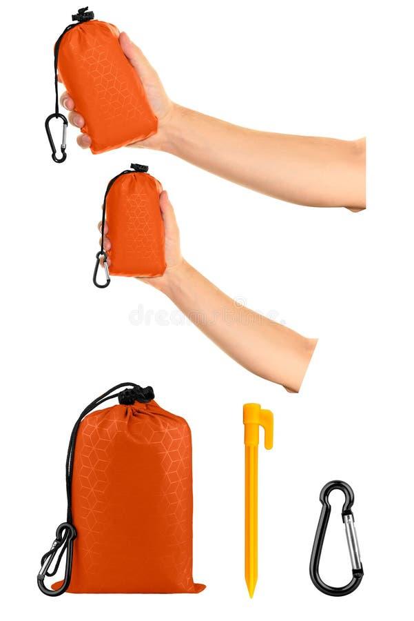 Очень компактное ручное оранжевое одеяло кармана нейлона в сумке drawstring, с пластиковыми кольями шатра и carabiner Тонкий брез стоковые изображения rf