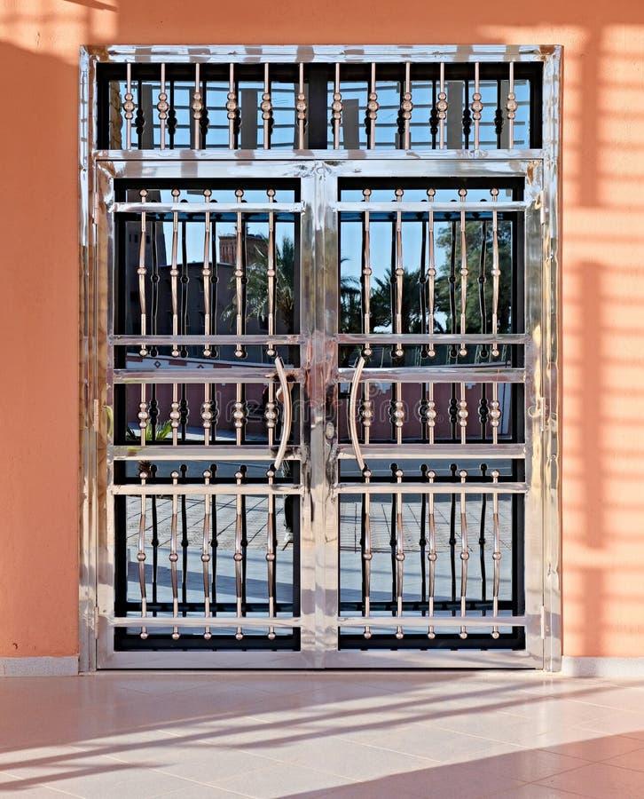 Очень красивая дверь, сделанная в самом современном стиле элементов стекла и металла зеркала с сияющей отполированной поверхность стоковые фото
