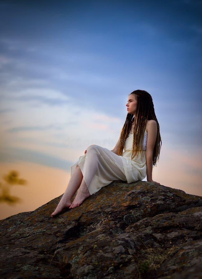 Очень красивая девушка с dreadlocks на утесе в светлом платье стоковые фотографии rf