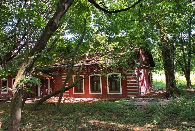 Очень красивый дом красного кирпича окруженный деревьями и травой стоковое изображение rf