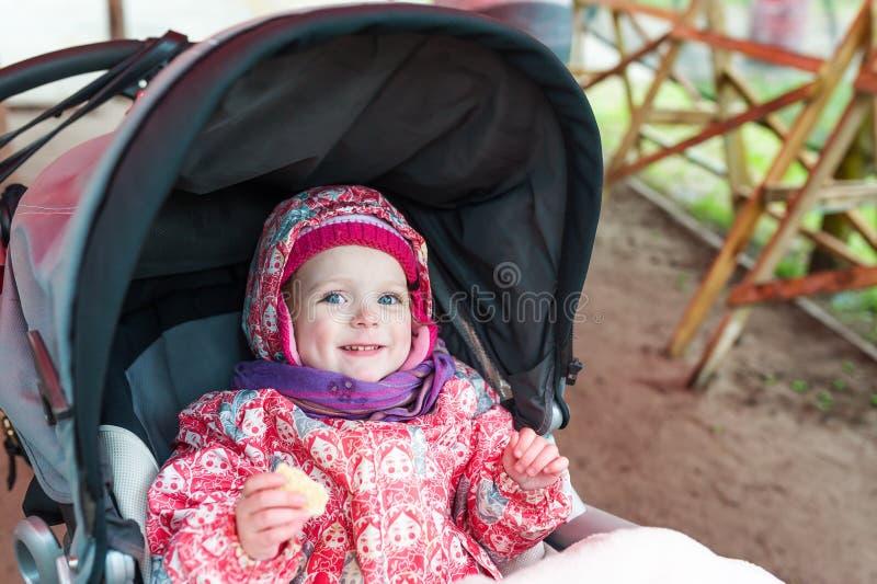 Очень красивый ребёнок сидя в pram и ждать маме стоковое изображение