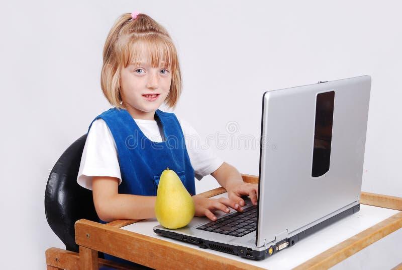 Очень милая белокурая девушка с компьтер-книжкой на изолированном столе стоковое изображение
